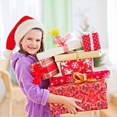 Girl (8-9) carrying christmas gifts