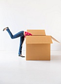 Studio shot of young woman looking into box