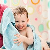 Mutter hält frisch gebadeten Sohn, in Handtuch eingewickelt