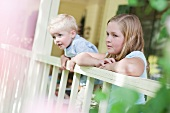 Brother and sister gazing over porch railing