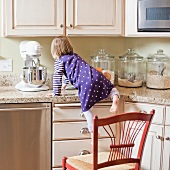 USA, Utah, Girl (2-3) climbing on cupboard in kitchen