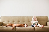 Girl (4-5 years) on couch with dog
