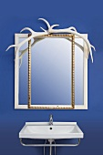 Mirror with white and gilt frames decorated with antler above sink