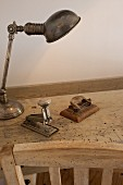 Silver desk lamp, hole punch and stapler on worm-eaten wooden table