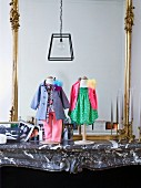 Dolls' clothes on stands on stone mantelpiece in front of gilt-framed mirror