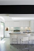 Bar stools with backs at a counter in a minimalist, white kitchen with large windows leading to the sunny garden