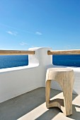 Wooden stool in corner of roof terrace below blue sky with view of sea