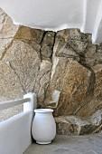 weiße Amphore in Ecke einer Terrasse vor geweisselter Steinbrüstung und Felswand