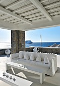 Cushions arranged on sofa with white loose cover and minimalist table and bench on roofed terrace in front of open sea