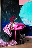 Folded bed linen on pink stool in front of modern painting