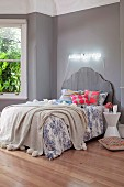 Bed with grey curved headboard, subdued blue and white bed linen and bright scatter cushions