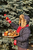 Woman decorating Christmas tree in garden