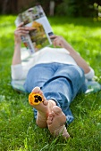 Woman lying on lawn reading magazine