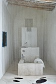 Fine bead curtain in front of stone bathtub in recess with wood-beamed ceiling