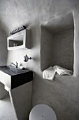 Stone washstand and niche in pale grey, limewashed wall in minimalist bathroom