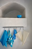 Blue bowl in limewashed niche; tea towels and bags hanging from hooks