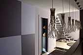 Pendant lamps with artistic lampshades in grey-painted hallway with view into stairwell