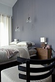 Chair with wooden back and ecru upholstered seat in front of double bed below pendant lamps with glass lampshades against grey wall