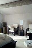Table lamp on modern stool flanked by armchairs against grey well in bedroom with wood-beamed ceiling