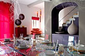 Festively set table in open-plan, modern interior with view of staircase through archway painted purple
