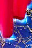 Fragments of blue tiles arranged as mosaic on floor and long red curtain lit form behind