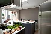 Gemüse auf Küchentheke unter Dunstabzug in Designer Küche in verschiedenen Grautönen