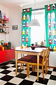 Dining table in kitchen with chequered floor & colourful curtains