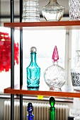 Decorative glass bottles of various shapes & colours on open shelving