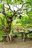 Terrace with metal plant stands in front of vintage garden bench and baskets and lanterns hanging from tree