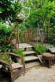 Old wicker chair next to wooden steps with rusty metal balustrade in garden with dense vegetation
