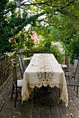 Tablecloth with lace insert and metal chairs on wooden terrace in garden with dense vegetation