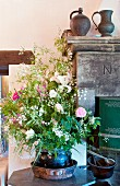Large bouquet in ceramic pot on table in front of old metal jugs on stone mantelpiece of partially visible fireplace