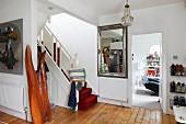 Treppe mit rotem Teppichbelag in tradionellem Vorraum mit Holzdielenboden