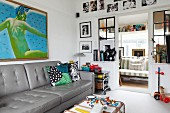 Grey leather couch below modern artwork on wall of living room and view into conservatory through open door