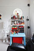 Child's table painted pale blue below shelves of toys next to robot standard lamp