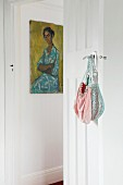 Vintage handbags on handle of traditional interior door and picture on wall in background