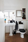 Bathroom with pedestal sink and toilet below window