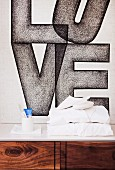 Modern mural of the word 'Love' behind stacked towels and toiletries