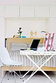 Weisser Klapptisch als mobiler Schreibtisch mit Laptop und Schreibtischlampe in modernem Schlafzimmer; beim Tisch ein Eames-Stuhl