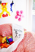 Scatter cushion with cover painted by child on bed in child's bedroom