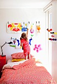 Little girl standing on bed in front of children's paintings on wall