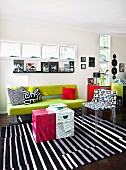 Bright, day-lit, modern living room with ribbon windows; spring green couch, designer chair and original coffee table made from printed cardboard boxes
