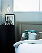 Black and white photo of Paris on black chest of drawers next to double bed with upholstered headboard and silk scatter cushions