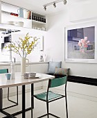 Minimalist dining area in front of open-plan kitchen with shelving suspended from ceiling above counter