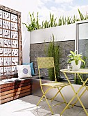 Kunstobjekt auf Holzbank und Wand mit integrierten Pflanztrögen hinter besonntem Freisitz mit Stahlmöbeln im Retrostil
