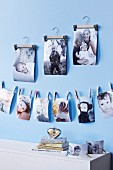 Family photos fixed on cord with mini clothes pegs and hung from small clothes hangers