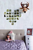 Collection of family photographs arranged in heart on wall next to amusing fake plush animal head