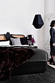 Black bed with decorative cane headboard and luxurious fur blanket in elegant bedroom with anthracite woollen rug and black pendant lamp