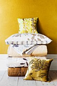 Folded, elegant quilts, bed linen and scatter cushions against golden yellow wall