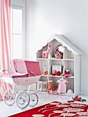Toys arranged in romantic dolls' house and pink retro dolls' pram